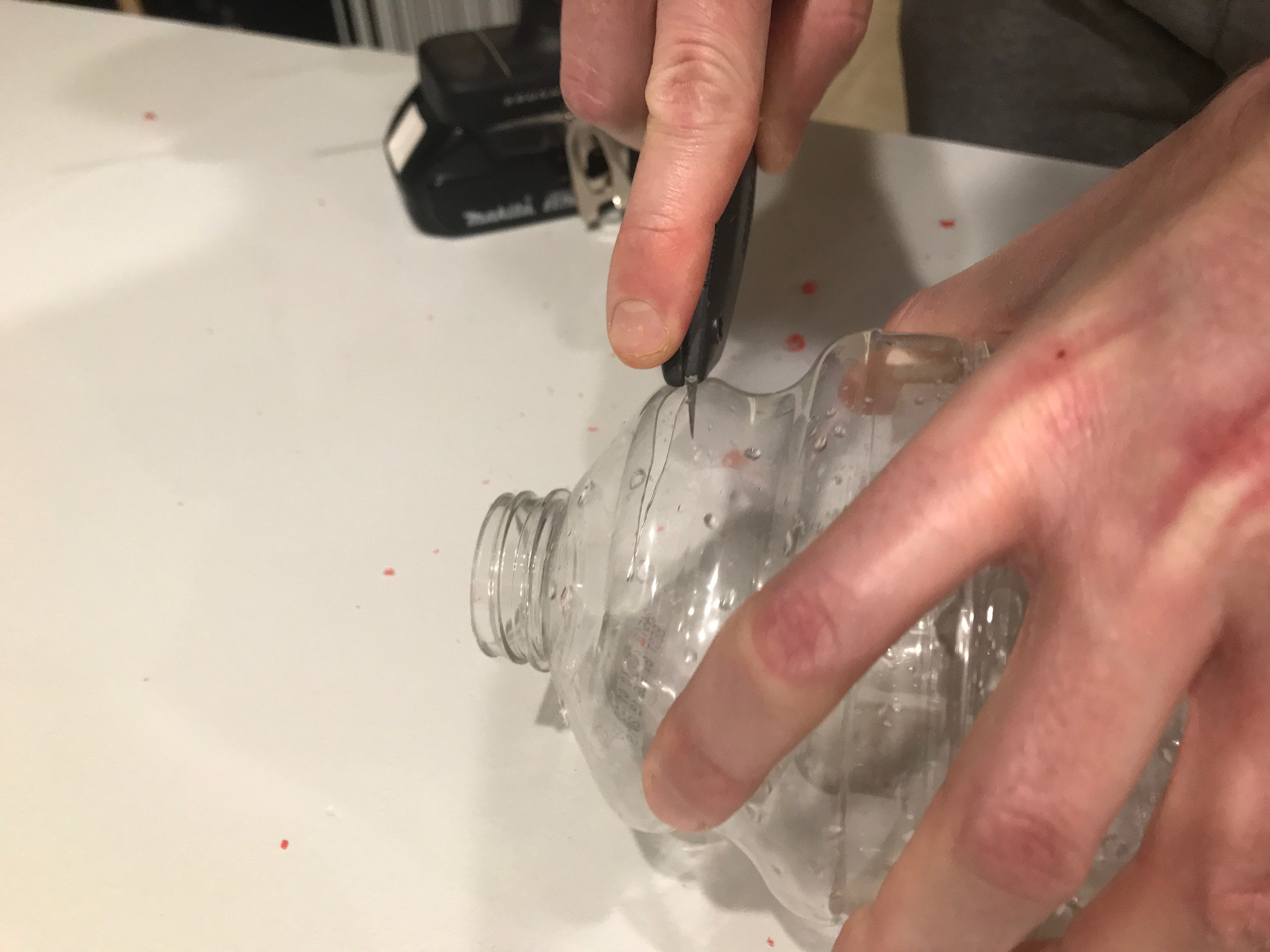 Bottle being cut with utility knife
